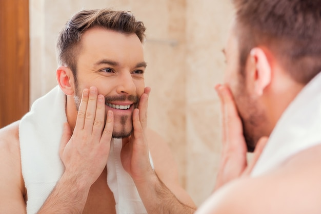 Taking good care of his face. handsome young man touching his face and smiling while standing in front of the mirror