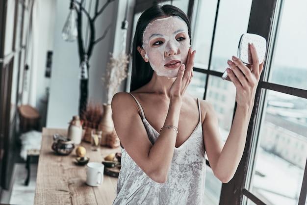 彼女の肌の世話をします。顔のマスクを適用し、鏡を見て魅力的な若い女性