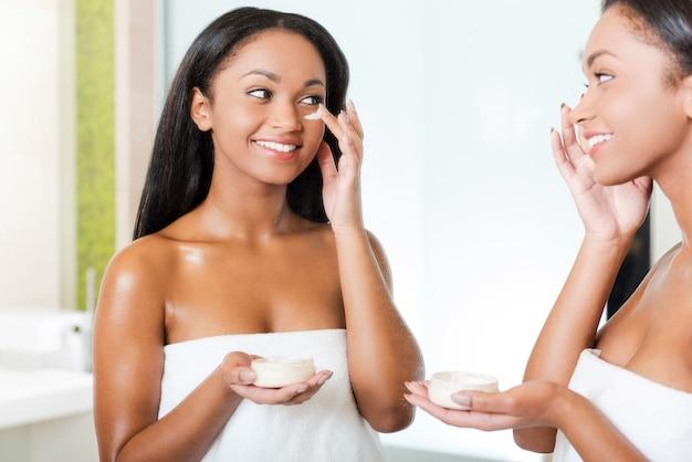 Заботится о своей коже. красивая молодая африканская женщина наносит крем на лицо и улыбается