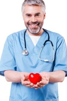 Заботьтесь о своем сердце. уверенный зрелый хирург-кардиолог держит игрушку в форме сердца и улыбается, стоя изолированным на белом