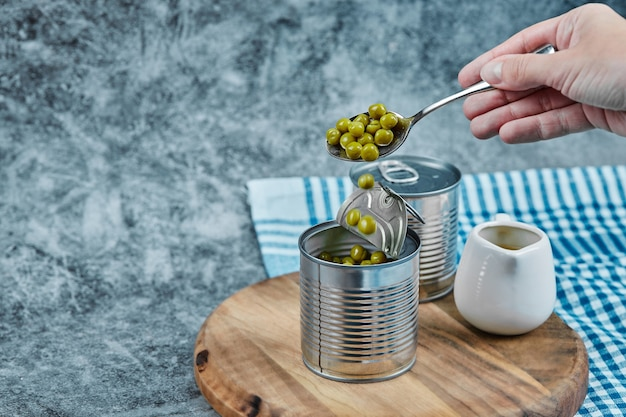 Taking green pea beans ouf of a metallic can.