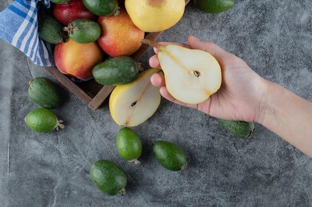 Prendendo una pera tagliata a metà dal vassoio della miscela di frutta