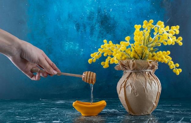 Prendendo il miele con il bastoncino dal piattino.