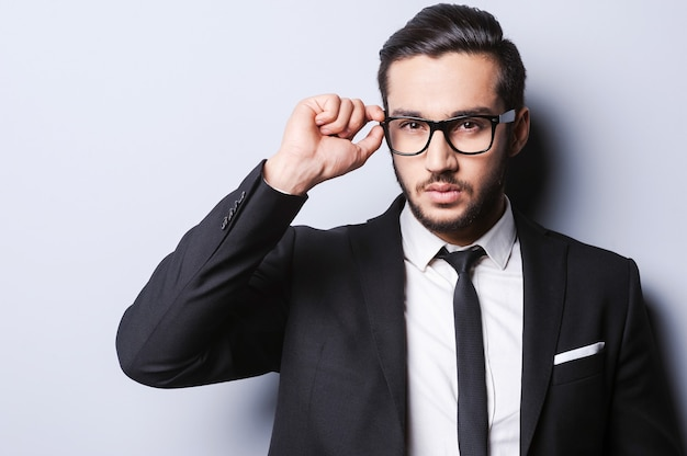 人生を真剣に受け止めています。灰色の背景に立っている間彼の眼鏡を調整する正装でハンサムな若い男の肖像画