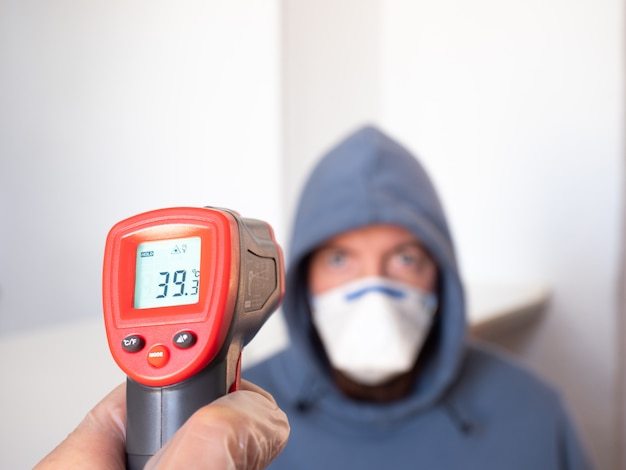 Taking a man's temperature with an infrared meter. high fever, symptom, disease.