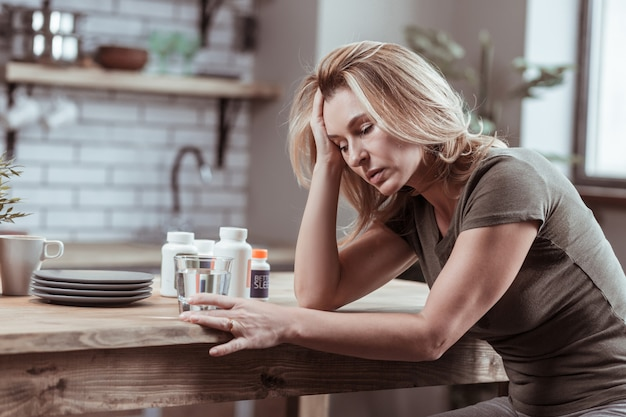Taking medicine. blonde-haired woman sitting in kitchen and taking medicine while feeling sick and tired