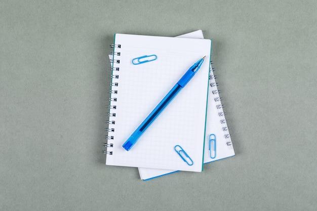 Presa delle note e concetto di contabilità con il taccuino, penna sulla vista superiore del fondo grigio. immagine orizzontale