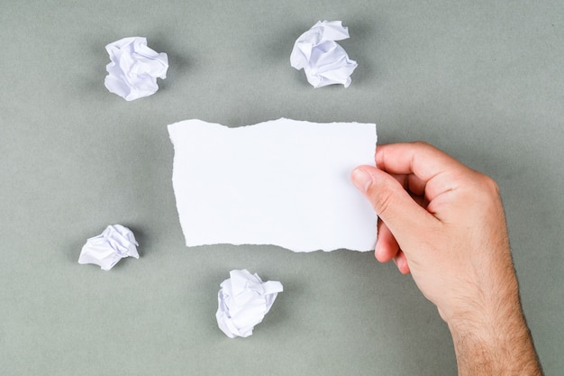 회색 배경 평면도에 메모를 복용 메모 개념을 관리합니다. 한 장의 종이 들고 손입니다. 텍스트를위한 여유 공간. 가로 이미지