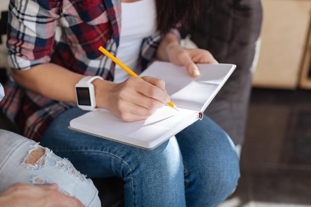 Делать заметки. крупным планом карандаш, который держит милая приятная женщина и использует для письма, делая заметки