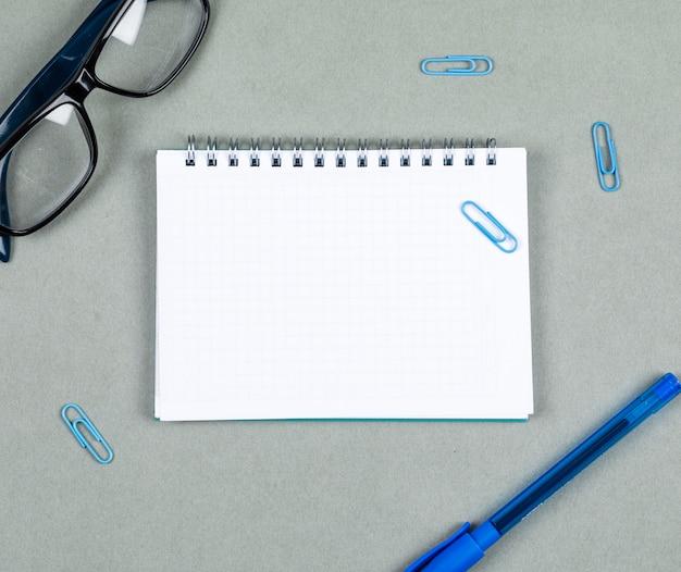 灰色の背景の上面にノート、ペン、眼鏡でノートコンセプトを取る。テキストのためのスペース。横長画像