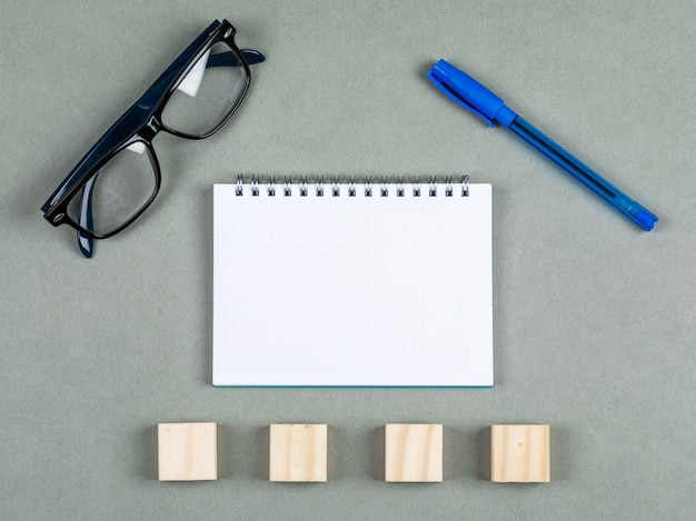 Taking notes concept with notebook, pen, eyeglasses, wooden elements on gray background top view. space for text. horizontal image