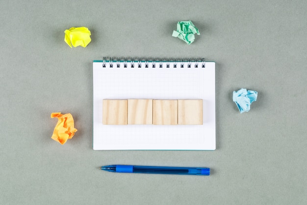 Taking notes concept with notebook, torn notes, wooden cubes on gray background top view. horizontal image
