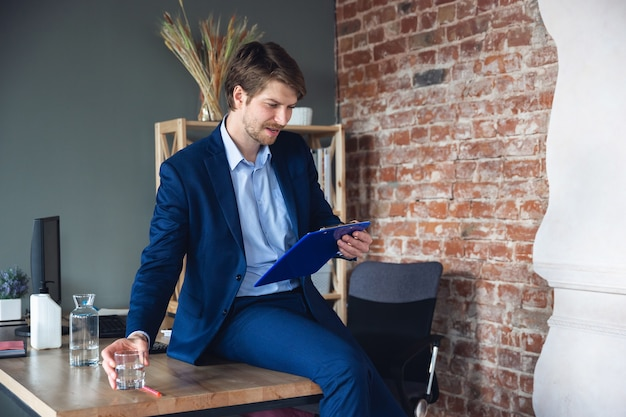 Taking notes daily tasks sitting on table young man manager return to work in his office