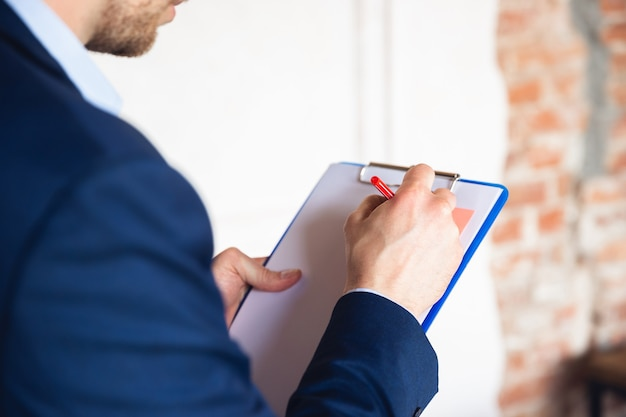 Taking notes daily tasks sitting on table young man manager return to work in office quarantine