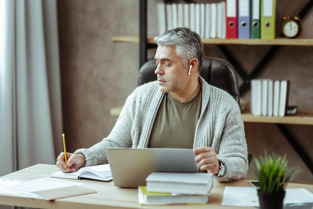 메모하기. 그의 노트북에 쓰는 동안 테이블에 앉아 심각한 좋은 사람