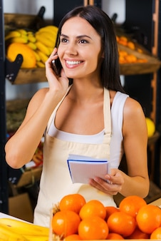 果物を注文する。さまざまな果物を背景に食料品店に立っている間、携帯電話で話し、メモ帳を持っているエプロンの陽気な若い女性
