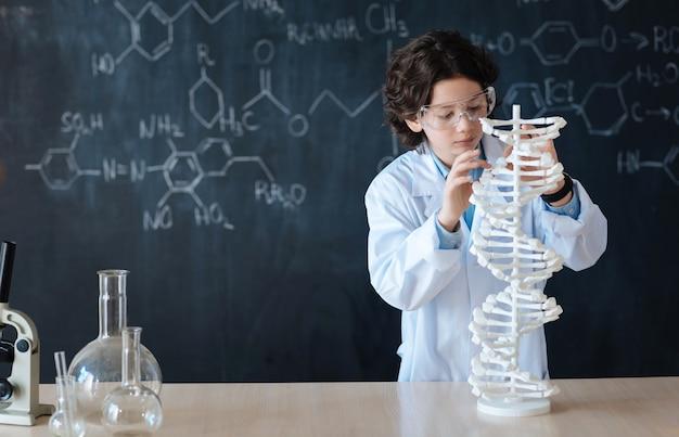 화학 프로젝트에 참여합니다. 수업을 듣고 화학 프로젝트에 참여하는 동안 학교 칠판 근처에 서있는 지능적인 부지런한 학생