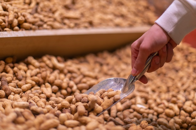 Taking peanuts from the stock at the grocery. high quality photo
