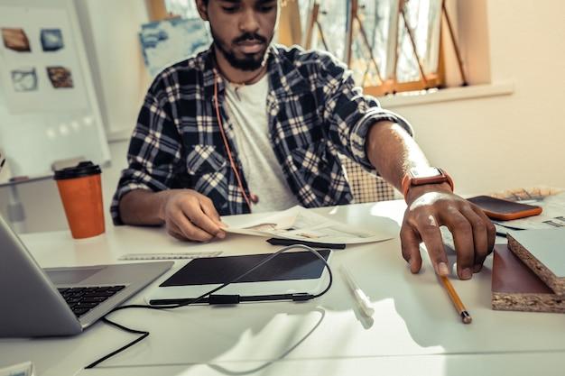 鉛筆を取る。スケッチを描きながら鉛筆を取る赤いスマートウォッチを身に着けている忙しいインテリアデザイナー