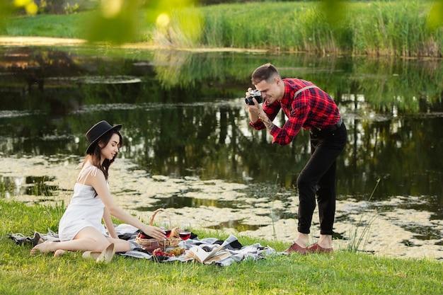 写真を撮ります。夏の日に公園で一緒に週末を楽しんでいる白人の若いカップル