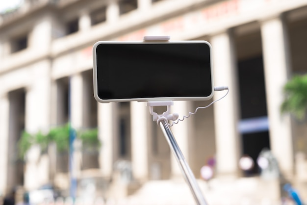 Taking picture by smart phone selfie stick. outdoors.