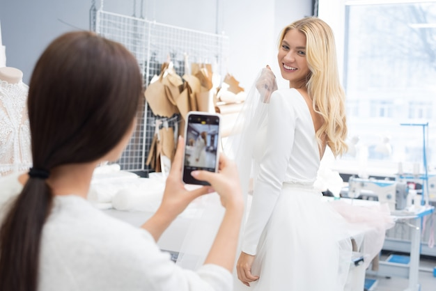 Taking picture of woman in bridal shop