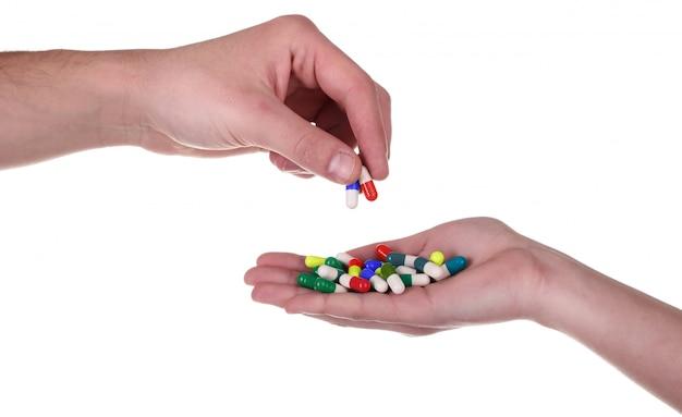 Принимая таблетки из рук, изолированные на белом