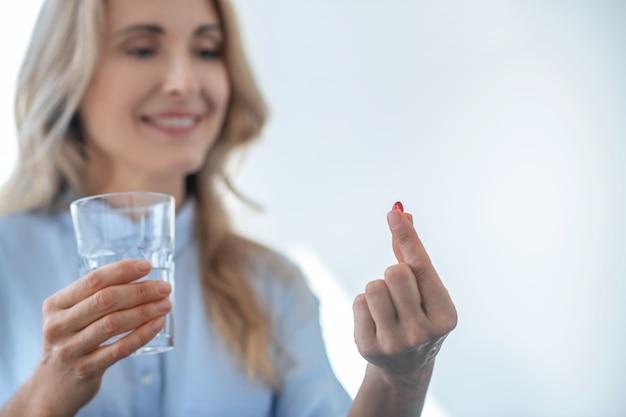 Принимая таблетки. блондинка женщина держит стакан воды, принимая красную таблетку