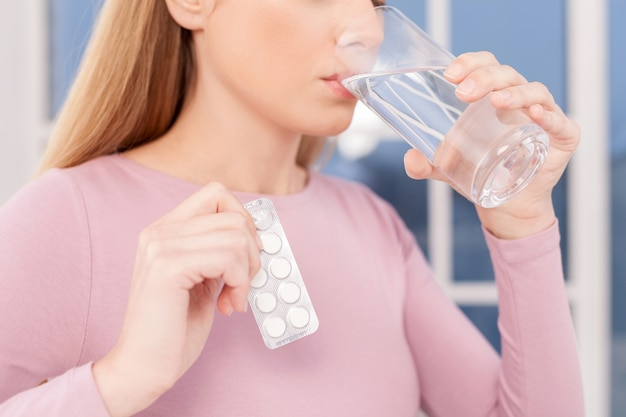 Принимая таблетки. обрезанное изображение молодой женщины, принимающей таблетки и питьевой воды