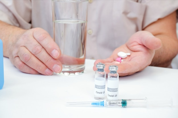 Taking pills, a glass of water in the hand of an elderly person