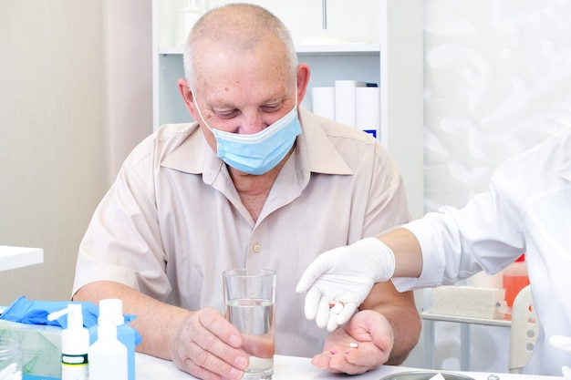 Taking pills, a glass of water in the hand of an elderly person.