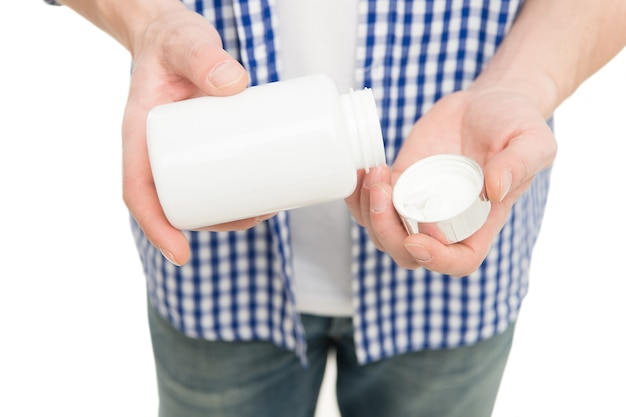錠剤を服用します。ヘルスケアと治療。ビタミンは免疫力を維持します。ビタミンサプリメントの概念。男性の手はボトルの薬やビタミンを持っています。大人のためのビタミン複合体。正しい投与量。男性の健康。