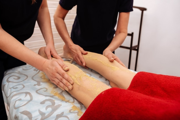 粉を取ります。黒の制服を着た女性が、冷える女性の足に癒しとスクラブパウダーを積極的にこすりつけている