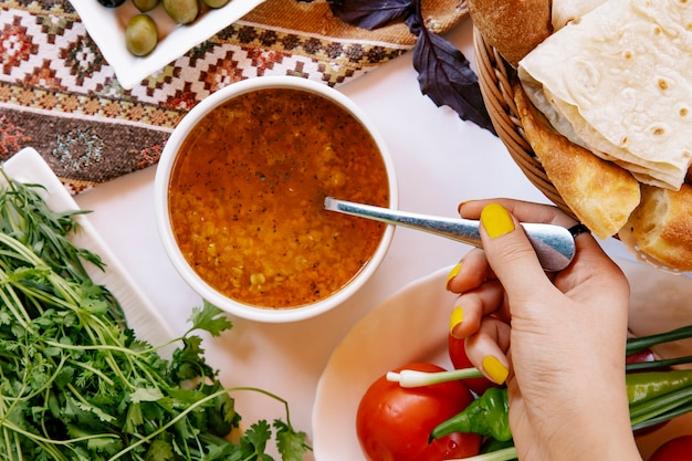 Taking russian borsch soup with a spoon.