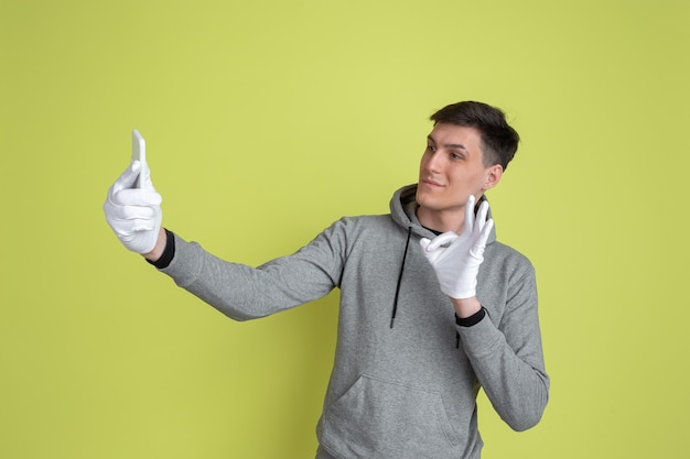 自撮り写真を撮ります。黄色の壁に分離された白人男性の肖像画。手袋を使用した気紛れな男性モデル。