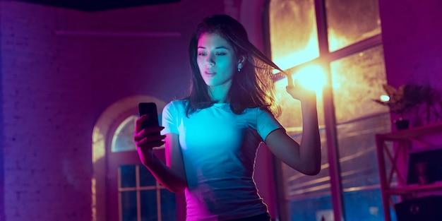 셀카 찍기. 네온 조명이 켜진 실내에서 잘생긴 세련된 여성의 영화적 초상화. 보라색 - 파란색의 영화 효과처럼 톤. 실내에서 화려한 조명으로 스마트폰을 사용하는 백인 모델입니다. 전단.