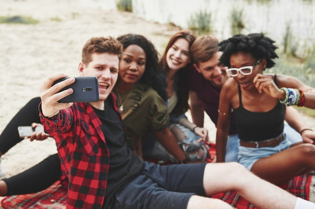 Taking selfie. group of people have picnic on the beach. friends have fun at weekend time.