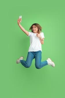 ジャンプで自分撮りをします。緑のスタジオの壁に分離された白人の若い女性の肖像画