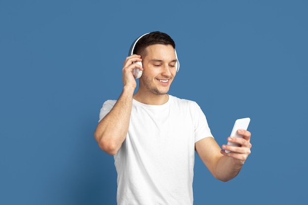 셀카를 찍고 음악을 듣습니다. 블루 스튜디오 배경에 백인 젊은 남자의 초상화. 캐주얼 스타일, 파스텔 색상의 아름다운 남성 모델. 인간의 감정, 표정, 판매, 광고의 개념.