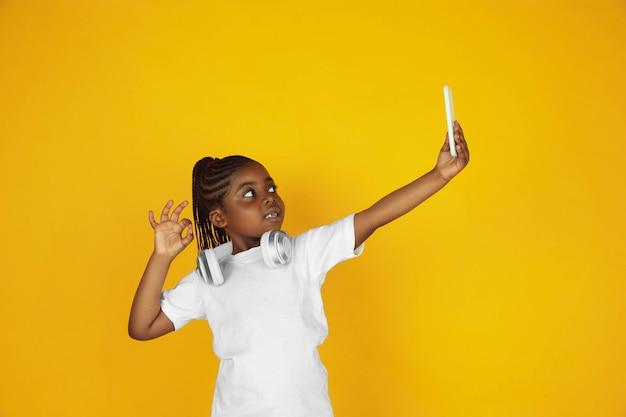 自撮り写真を撮り、音楽を聴きます。黄色のスタジオの背景に小さなアフリカ系アメリカ人の女の子の肖像画。元気な子。人間の感情、顔の表情、販売、広告の概念。コピースペース。かわいく見えます。