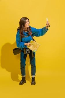 自撮り写真やブログを撮る。黄色のスタジオの背景に分離されたバッグと双眼鏡で陽気な若い白人観光の女の子の肖像画。旅行の準備。リゾート、人間の感情、休暇。