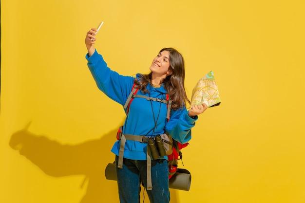 Селфи или видеоблог. портрет веселой молодой кавказской туристической девушки с сумкой и биноклем, изолированных на желтом фоне студии. подготовка к путешествию. курорт, человеческие эмоции, отдых.