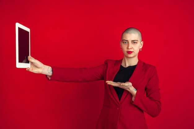 셀카 또는 동영상 블로그를 찍습니다. 빨간 벽에 고립 된 젊은 백인 대머리 여자의 초상화. 재킷에 아름 다운 여성 모델입니다. 인간의 감정, 표정, 판매, 광고 개념. 이상한 문화.