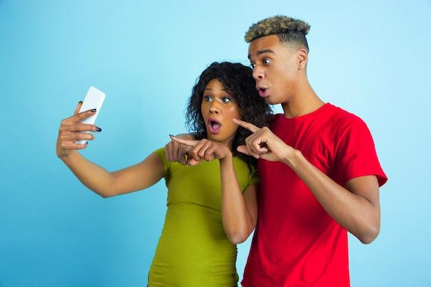 셀카 나 동영상 블로그를 함께 찍습니다. 파란색 배경에 화려한 옷에 젊은 감정적 인 아프리카 계 미국인 남자와 여자. 아름다운 커플. 인간의 감정, 얼굴 expession, 관계, 광고의 개념.