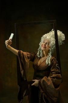 셀카 찍기. 어두운 배경에 나무 프레임 빈티지 의류에서 중세 젊은 여자의 초상화. 공작 부인, 왕실 사람으로 여성 모델. 시대, 패션, 아름다움의 비교 개념.