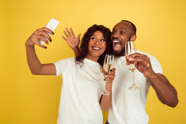 Facendo selfie insieme. celebrazione di san valentino, felice coppia afro-americana isolata su sfondo giallo.