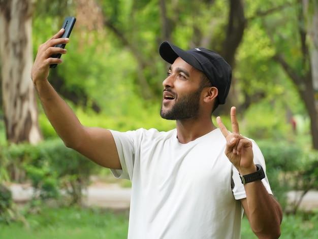 Делая селфи с помощью мобильного телефона и показывая знак победы