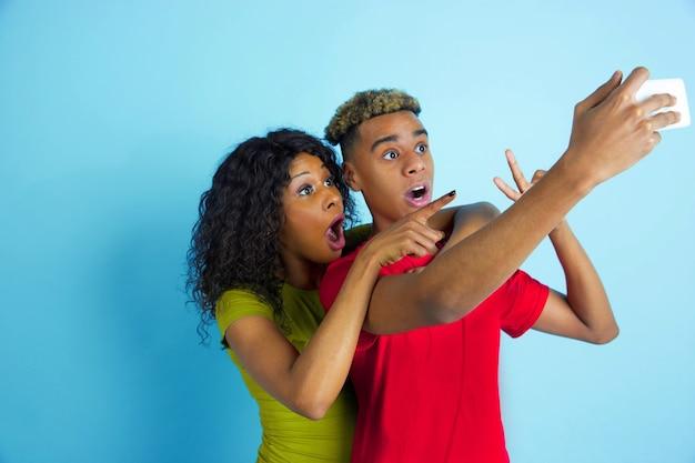 Fare selfie o vlog insieme. giovane uomo afro-americano emotivo e donna in abiti colorati su sfondo blu. bella coppia. concetto di emozioni umane, espansione facciale, relazioni, annuncio.