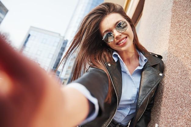 셀카 찍기. 따뜻한 옷을 입은 젊은 아름다운 소녀가 주말 시간에 도시를 산책했습니다.