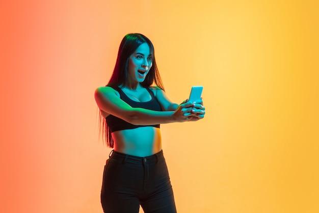 自撮り写真を撮ります。ネオンの光のグラデーション黄橙色のスタジオの背景に若い白人女性の肖像画。若者の概念、人間の感情、表情、販売、広告。スポーティーフィットモデル。